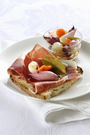 Grilled bread topped with Tuscan raw ham and pickled vegetables