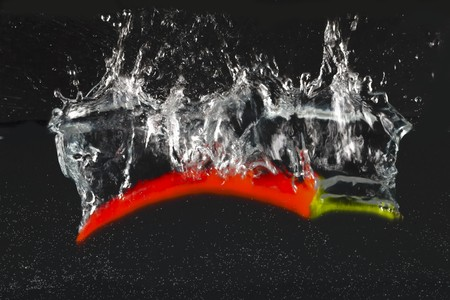 A chilli pepper falling into water