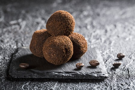 Truffle pralines with coffee beans on a black stone LANG_EVOIMAGES