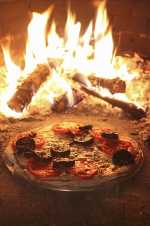 woodfired: Stone-baked pizza with cheese, tomatoes and black pudding in a woodfired oven LANG_EVOIMAGES