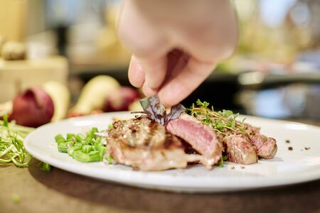 bean sprouts: Grilled beef steak being garnished