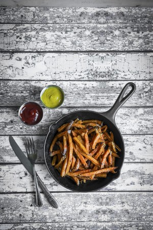 cast off: Sweet potato fries in cast iron pan on a rustic wooden surface
