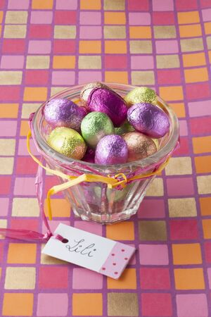 foil: Chocolate Easter eggs in coloured foil in a glass bowl with a gift tag