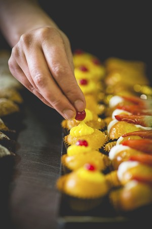 Mini cupcakes being decorated with red currants