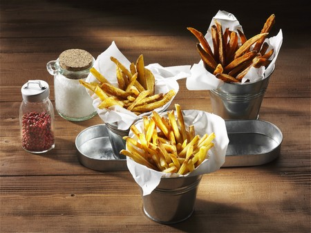 yam: Three types of chips with a salt shaker and pink pepper on a rustic wooden surface