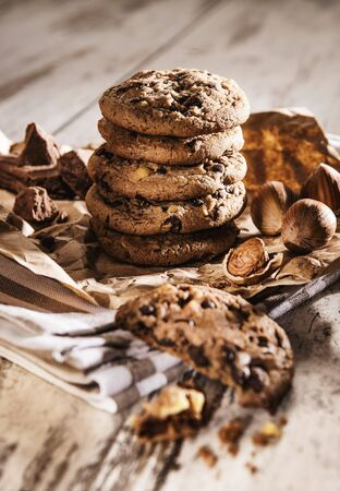 Chocolate chip cookies and hazelnuts on a piece of brown paper and a tea towel