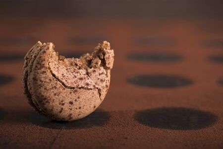 A chocolate macaroon with a bite taken out LANG_EVOIMAGES