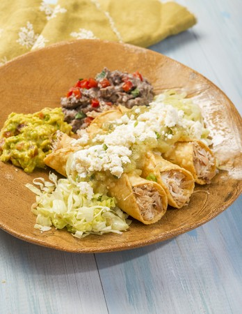Taquitos with chicken, guacamole, queso fresco and bean pur?e (Mexico) LANG_EVOIMAGES