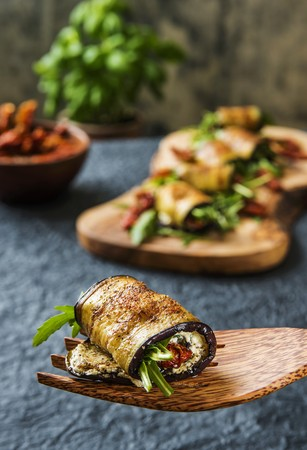 Aubergine rolls filled with sheeps cheese, rocket and dried tomatoes on a wooden fork and a wooden board LANG_EVOIMAGES