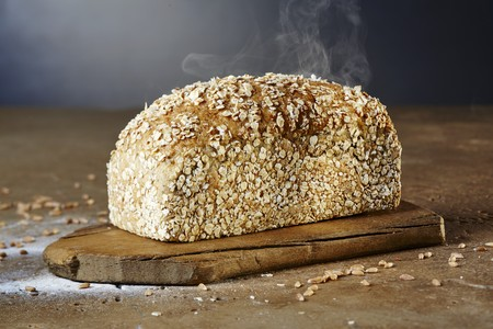 cutting: A steaming loaf of chia-spelt bread on a chopping board