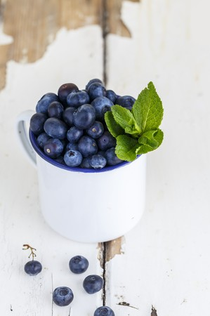 Blueberries and peppermint leaves in a white enamel cup