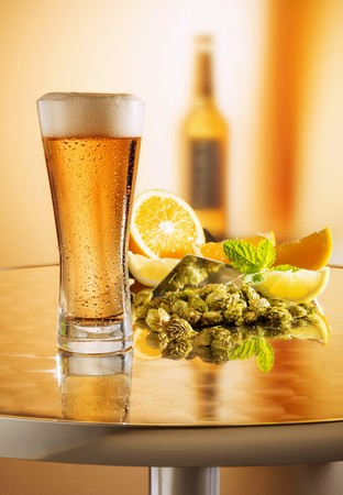 Freshly drawn beer in a glass on a metal table in front of an arrangement of hops, lemons and a beer bottle LANG_EVOIMAGES