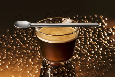 Glass of espresso with a spoon on a reflective surface with coffee beans