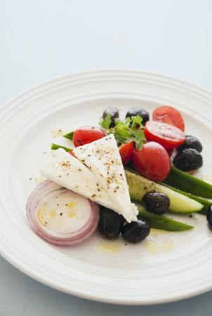 black and white photograph: Greek salad on a white plate LANG_EVOIMAGES