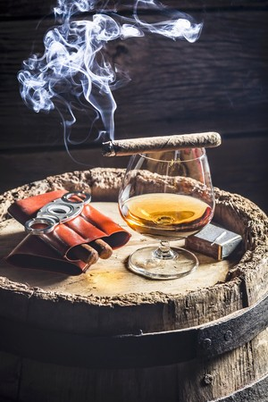 A glass of cognac and cigars on an old wooden barrel