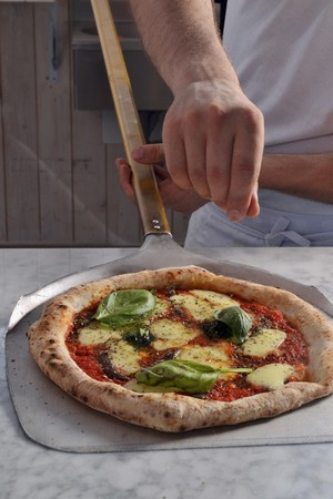 provenance: A pizza baker seasoning a pizza LANG_EVOIMAGES
