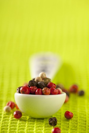 spice: Various different coloured peppercorns on a spoon LANG_EVOIMAGES