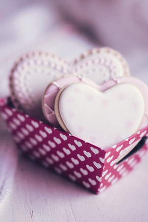 pinky: Pastel coloured heart-shaped biscuits in a paper box decorated with hearts