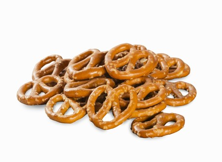 A pile of mini salted pretzels on a white surface LANG_EVOIMAGES