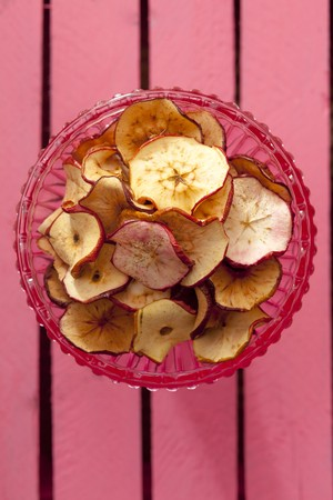 pinky: Homemade apple chips in a glass bowl (seen from above)