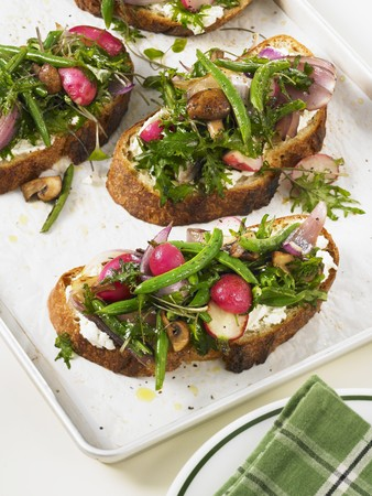 Slices of bread topped with cream cheese, beans, radishes and mushrooms