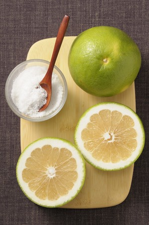 A grapefruit and sugar on a wooden board LANG_EVOIMAGES