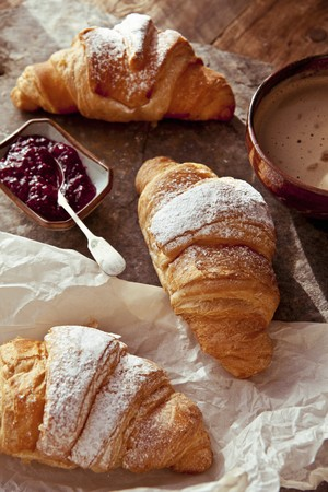 Butter croissants with raspberry jam and a cappuccino LANG_EVOIMAGES
