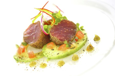Tuna fish medallions with a crumb crust served with avocado, tomatoes and wasabi sauce LANG_EVOIMAGES