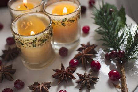 ides: Three candles in glasses decorated for Christmas with bilberries and star anise