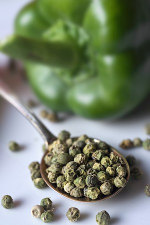 Dried green peppercorns on a spoon with a pepper in the background