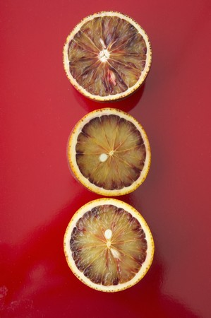ascorbic acid: Three blood orange halves on a red surface
