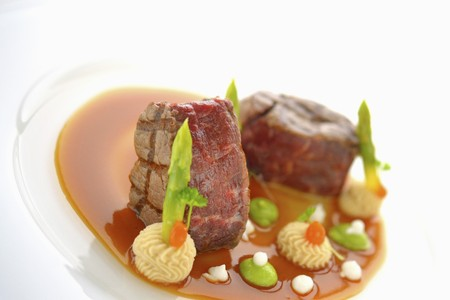 Wagyu beef loin steak in a pool of sauce with mashed potatoes and mushy peas