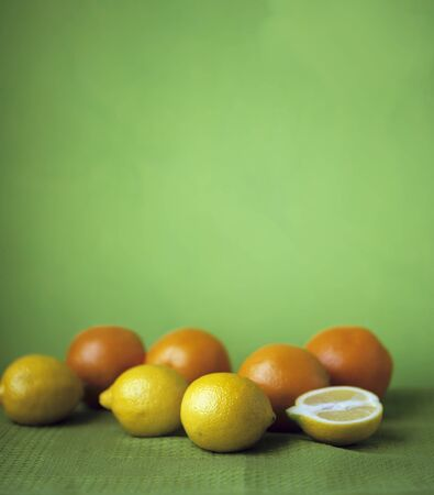 Lemons and oranges on a green surface