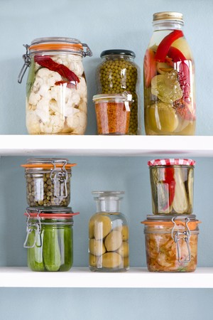 Various jars of preserved vegetables on a shelf