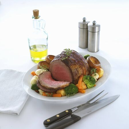 roast beef joint with vegetables and yorkshire puddings