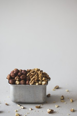 Hazelnuts and walnuts in a metal container