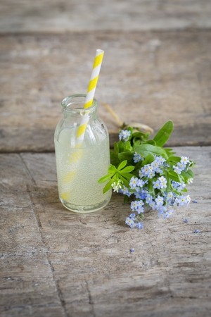 Rhubarb lemonade in a mini glass bottle next to a bouquet of forget-me-nots LANG_EVOIMAGES