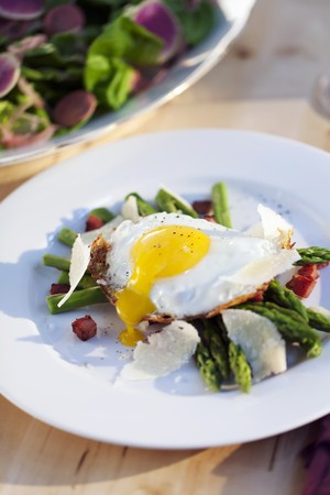 pancetta cubetti: Fried egg on green asparagus with diced bacon and Parmesan cheese