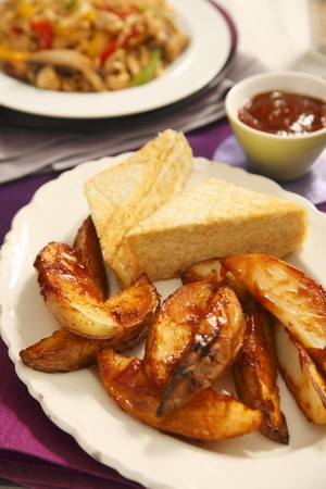Roast potato wedges with a chilli sauce and a piece of tofu LANG_EVOIMAGES
