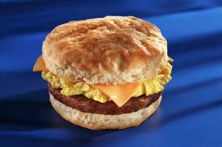 Fried sausage, cheese and scrambled egg on an American biscuit LANG_EVOIMAGES