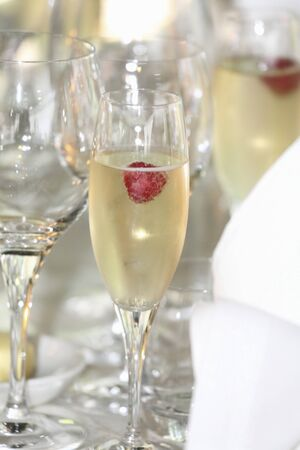 alcohol series: Raspberries in glasses of champagne on a table at a wedding