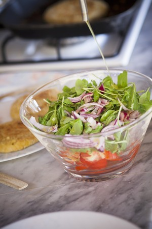 Green salad with red onions and tomatoes being drizzled with olive oil LANG_EVOIMAGES
