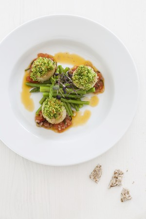 Scallops with a herb crust on a green asparagus salad with a tomato dressing