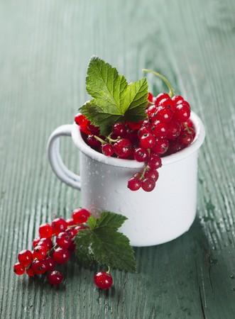 varnished: Red currants in an enamel mug
