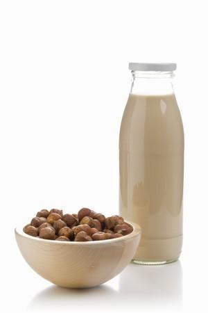 A bottle of hazelnut milk and a bowl of hazelnuts LANG_EVOIMAGES