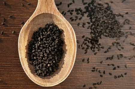 nigella seeds: Black caraway seeds on a wooden spoon (seen above)