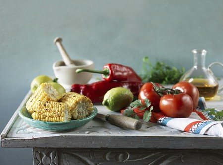 An arrangement featuring grilled corn cobs, tomatoes, peppers, lemons and oil LANG_EVOIMAGES