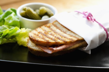 A ham and cheese panini wrapped in paper LANG_EVOIMAGES