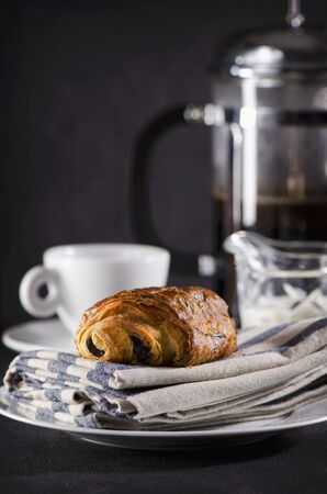 bakery products: A chocolate croissant and a cup of coffee LANG_EVOIMAGES