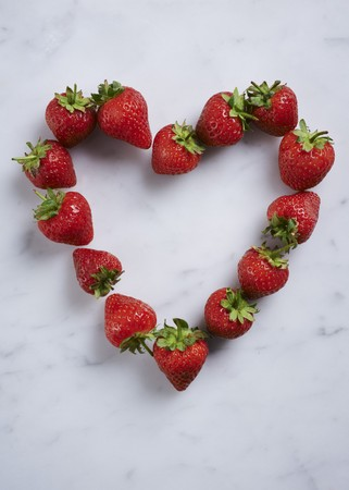 whiteness: A heart of fresh strawberries on a white surface